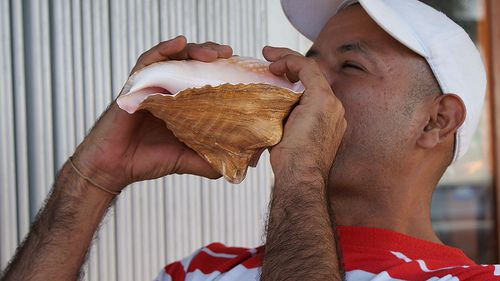 Blowing on a conch shell.