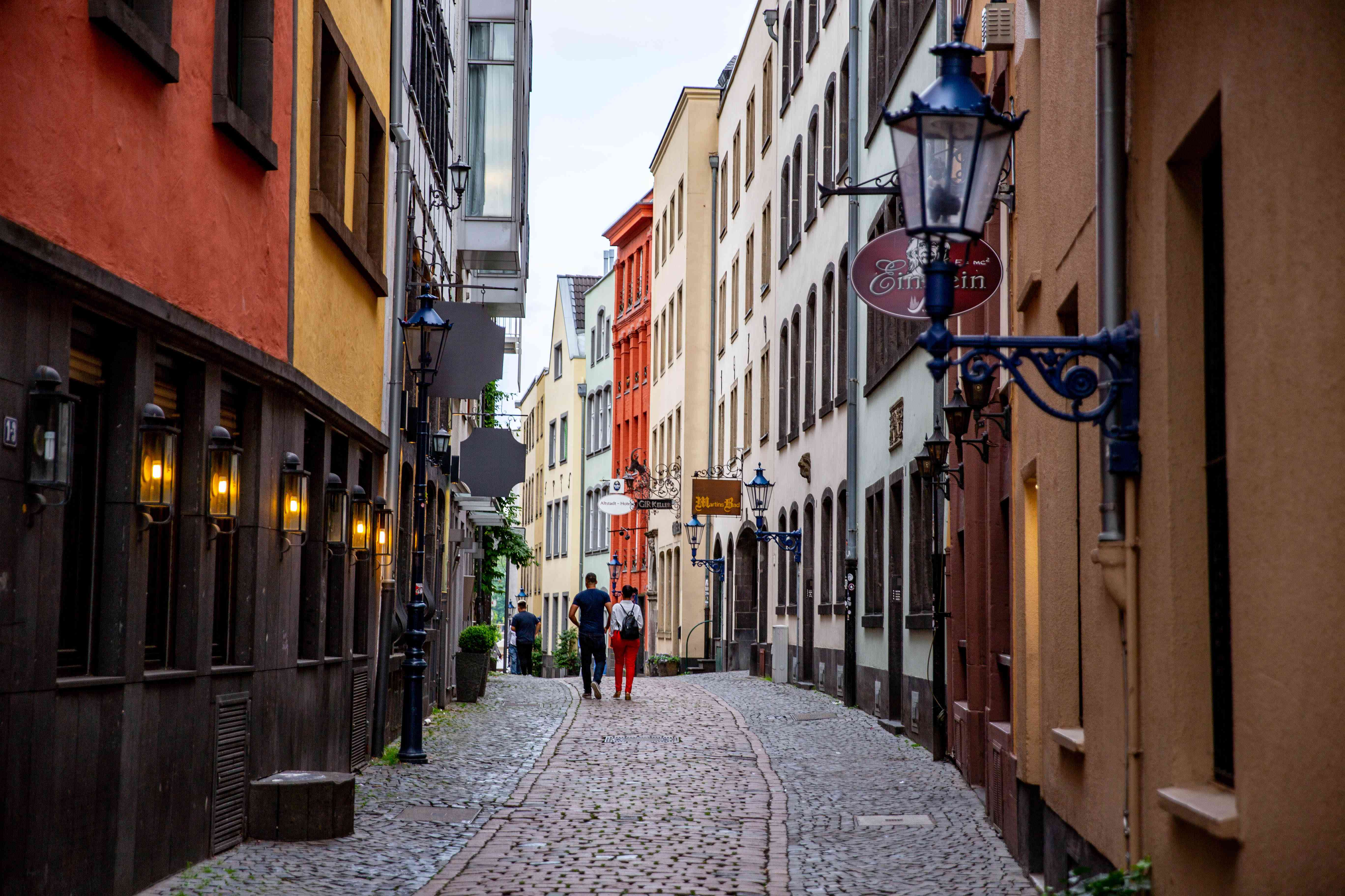 People walking down a cobblestone street in the Old Town of COlogne