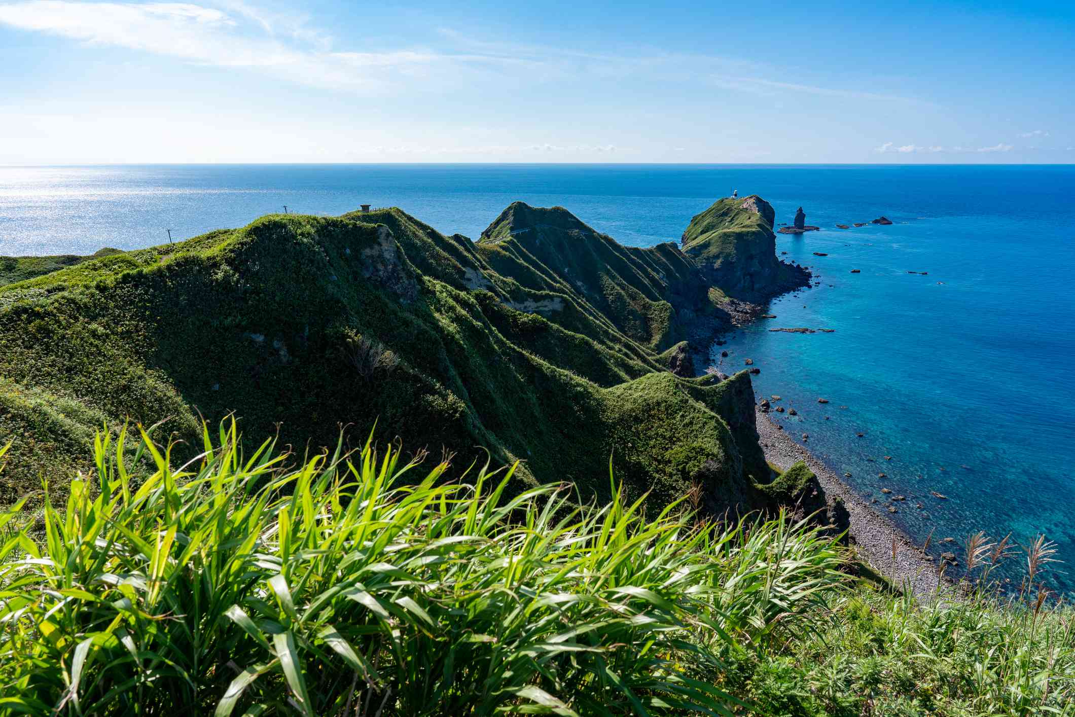Rivew of the craggy, grass covered Shakotan Peninsula surrounded by turquosie blue water