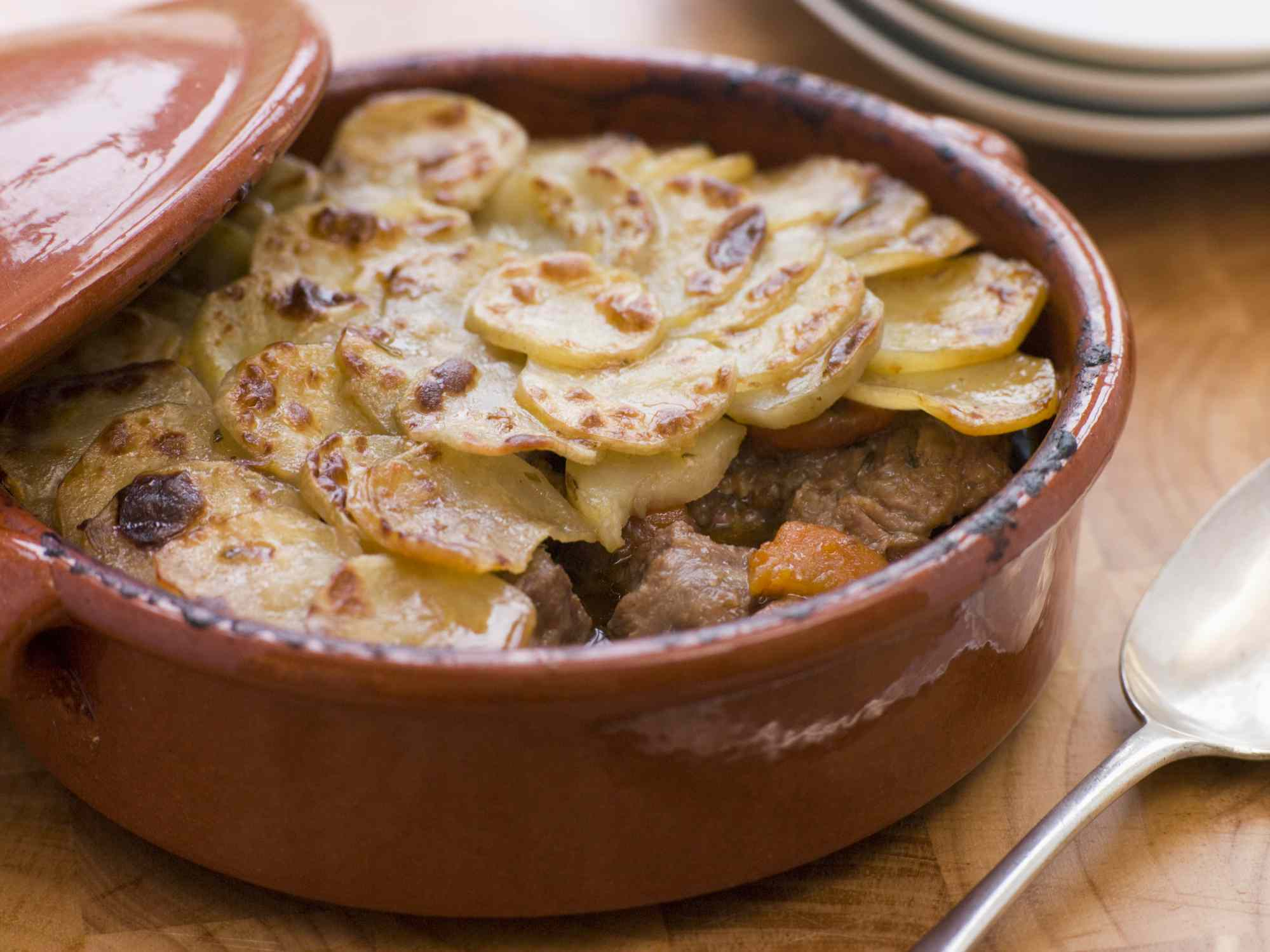 baking dish of a beef stew with thin-sliced potatoes layered on top