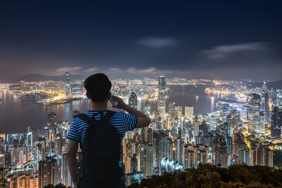 Chinese young man using smart phone and looking at cityscape of Hong Kong at night.