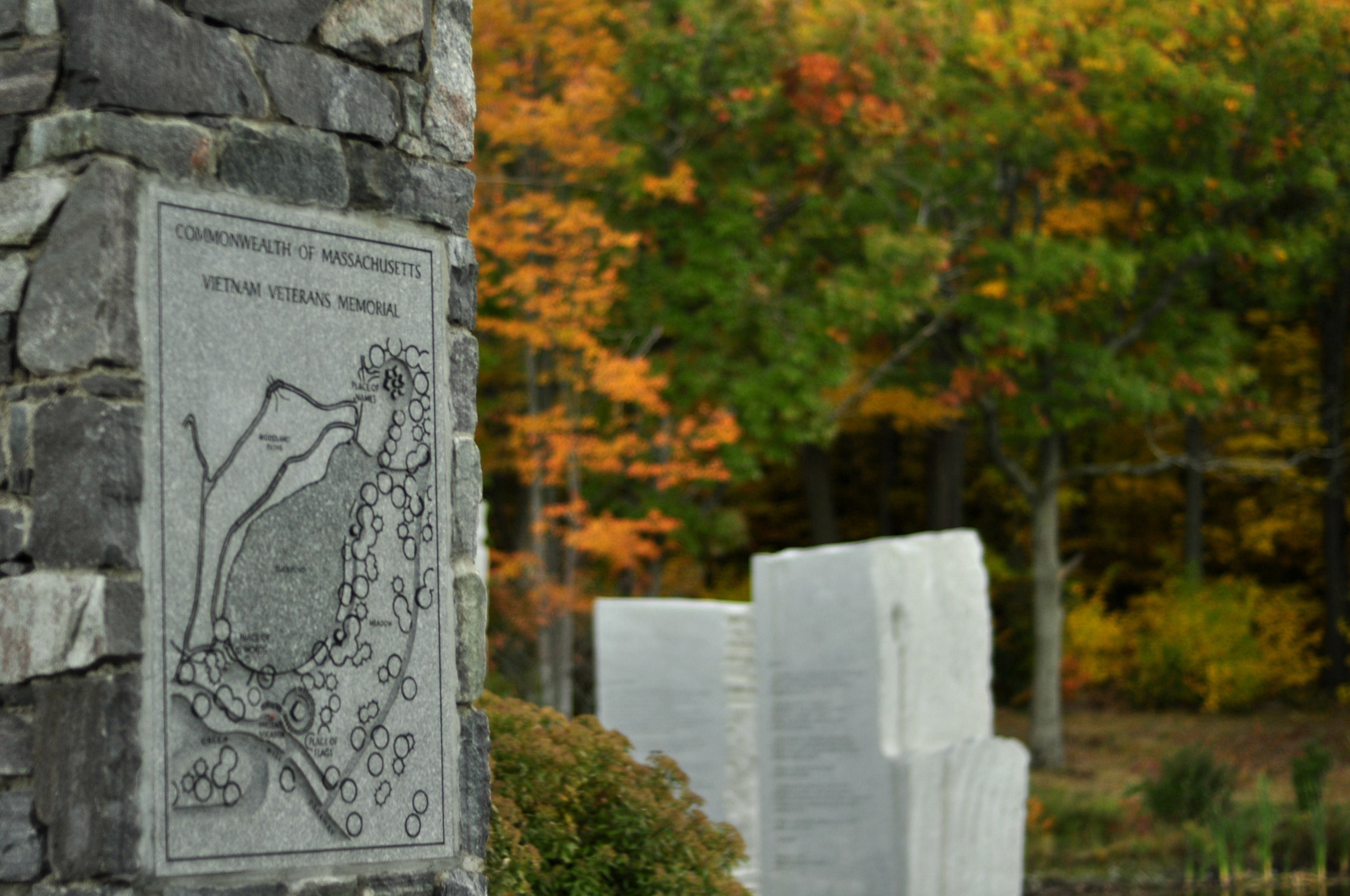 Engraved stone column monument at Worcester Vietnam Veteran Memorial with additional stone columns in the background.