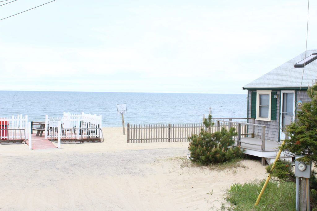 Beach with a small house and view of the water near Cape Cod