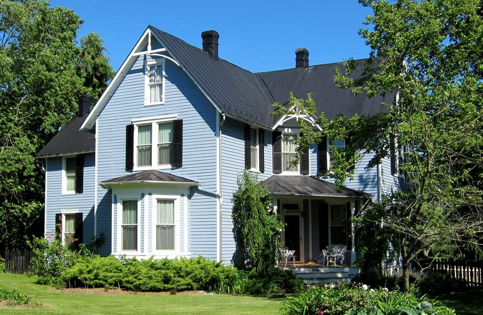 A blue-colored Folk Victorian style home