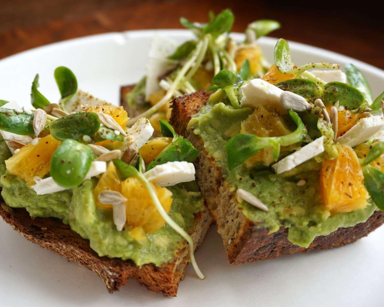 Avocado toast orange slices, sunflower seeds, ricotta salata, sunflower sprouts, citrus vinaigrette and za'atar spice on a white plate
