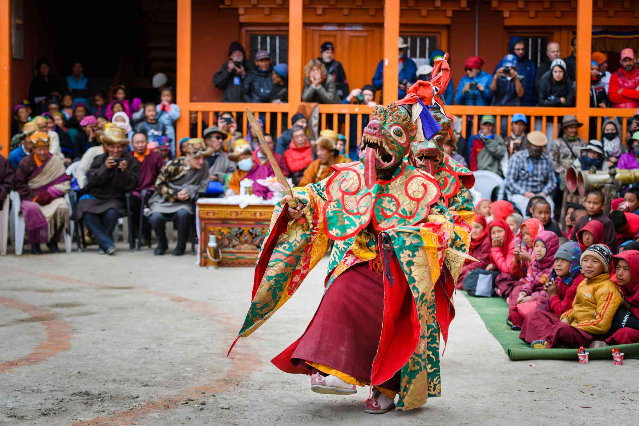 masked dancer wearing animal mask and colorful roes dancing in a courtyard surrounded by people watching