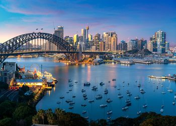 Sydney Harbour at sunset with bridge, city skyline and boats on the water