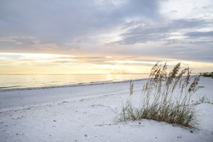 An empty white beach in Naples, Florida at sunset