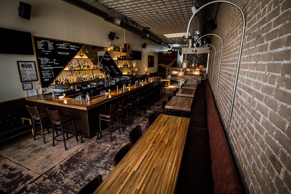 Long wooden tables and bar with a distressed floow and brick walls at Shoals Sound & Service