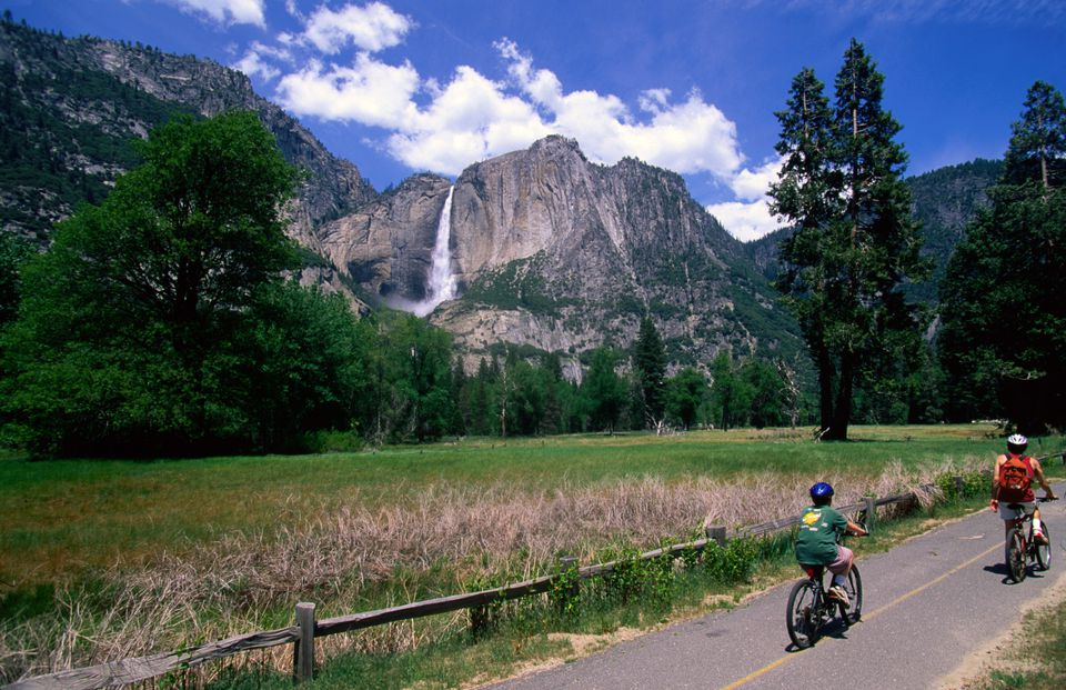 two people ridinng bikes on a paved trail with Yosemite Falls in the background