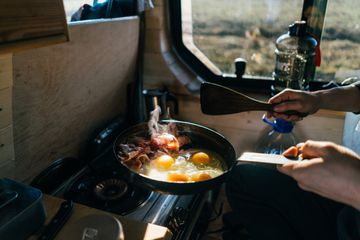 Cooking eggs and bacon in skillet at campsite