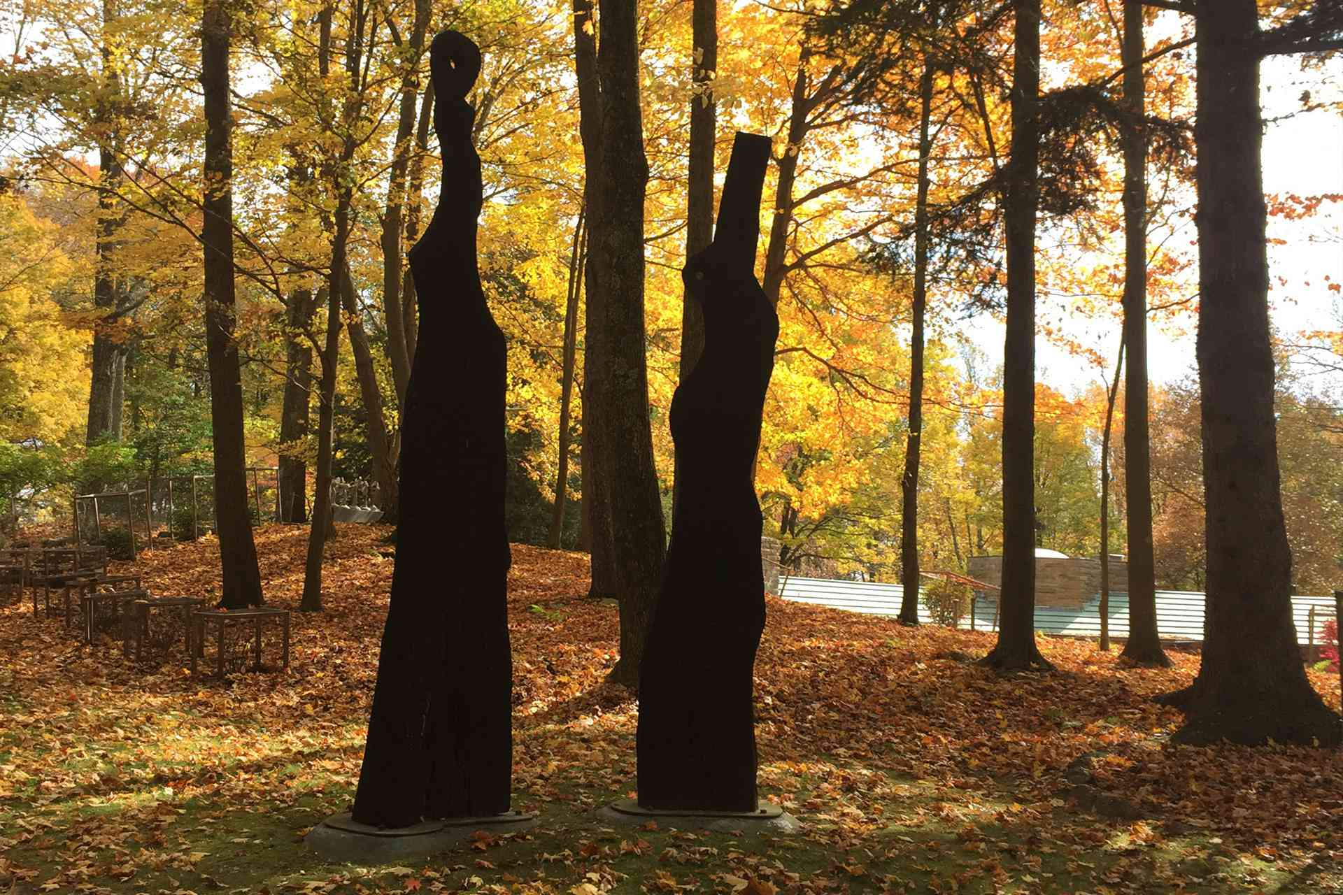 two dark abstract scuplptures in a wooded area at autumn