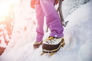pink pants, winter boots, crampons in the snow