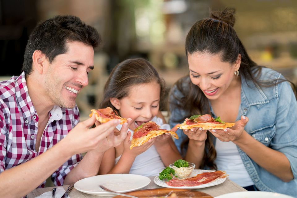 A picture of a family eating at a restaurant