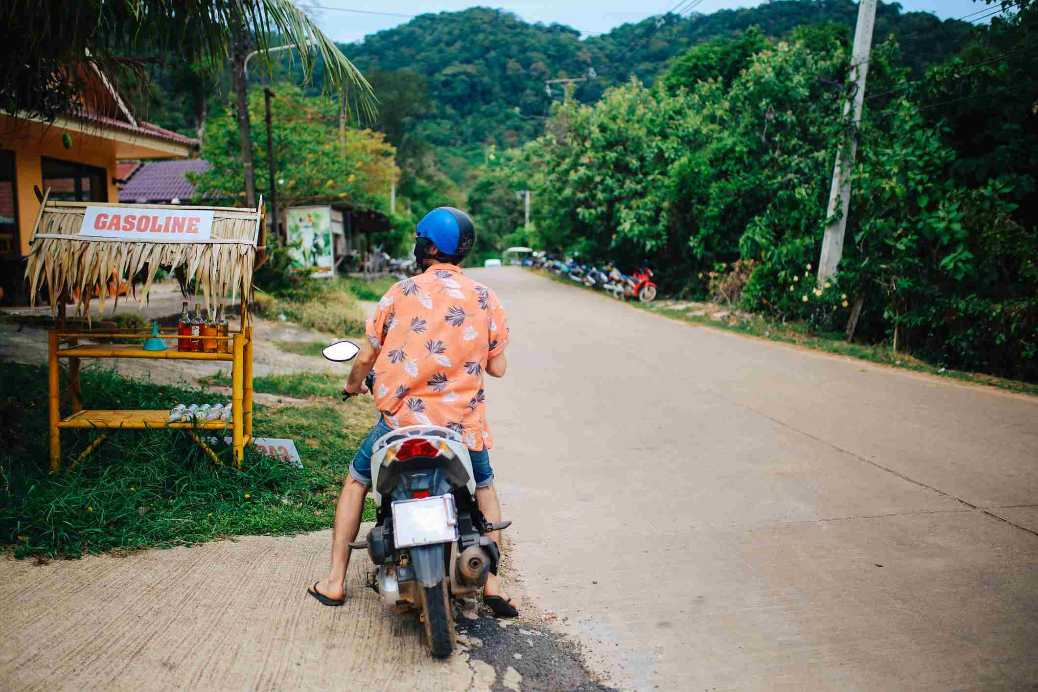 A man on a motorbike stops at a small gasoline stand, Koh Lanta