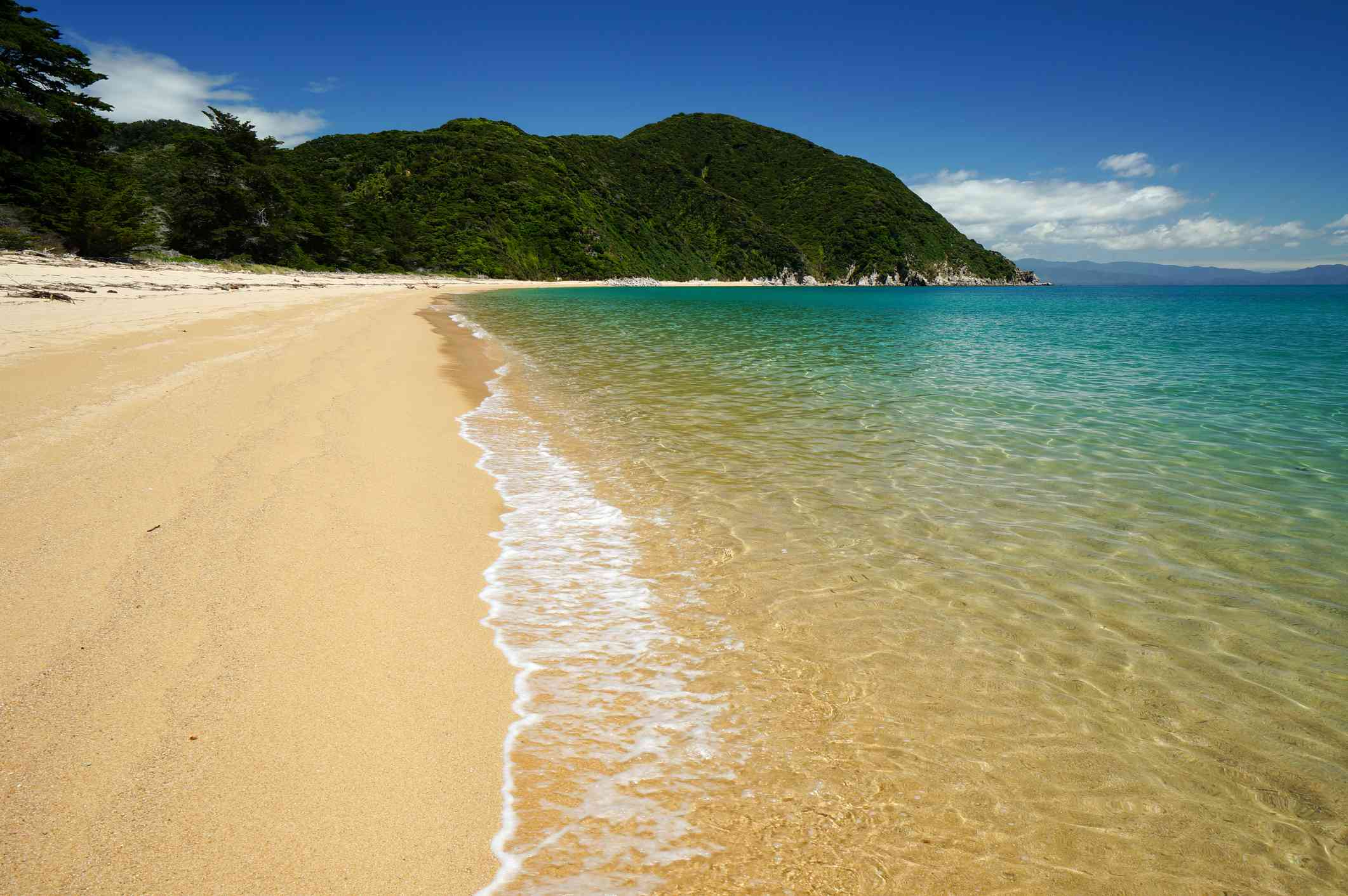 Gold sand beach with clear turquoise sea and forested hills behind