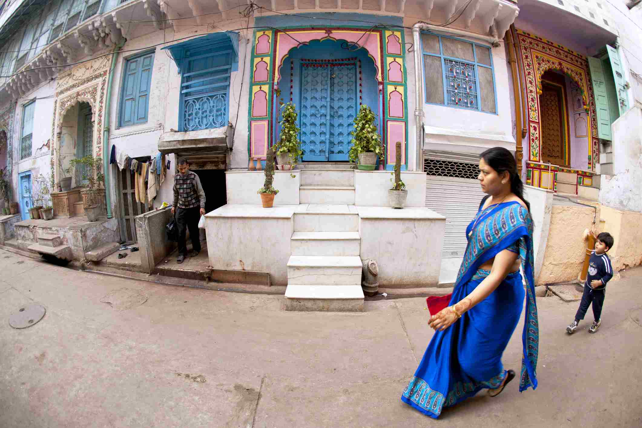 Woman and boy pass decorative houses in Naughara