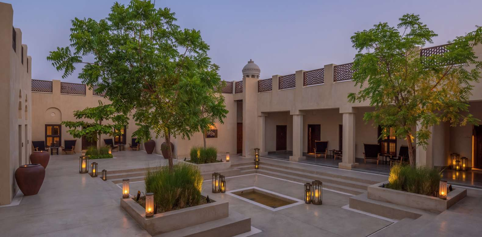 Courtyard in an Arabic architectural style with trees and many small lanterns