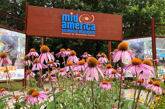 The sign at the entrance with flowers in front of the sign