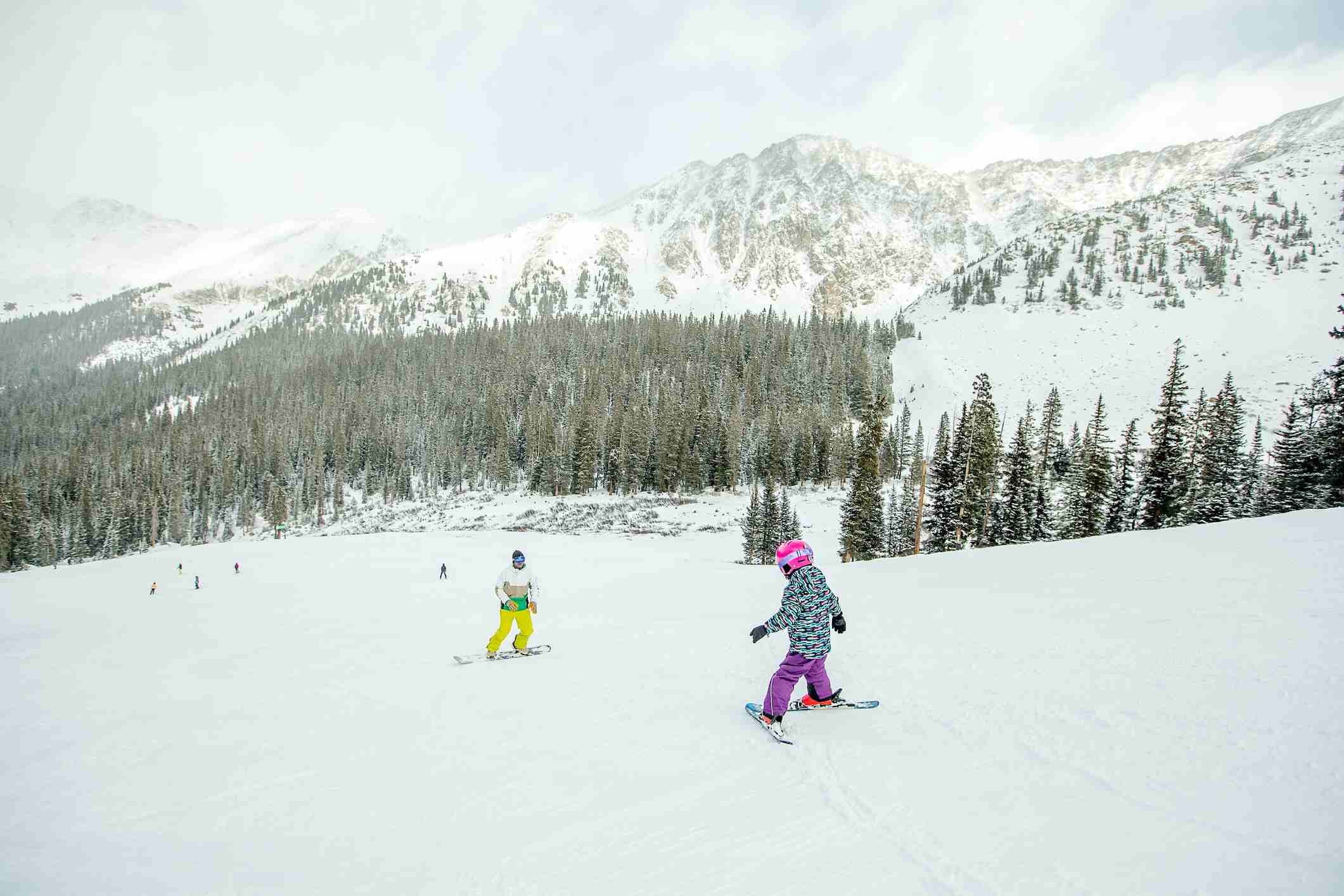 Young girl skiing toward her father on a steep slope in Keystone, Colorado