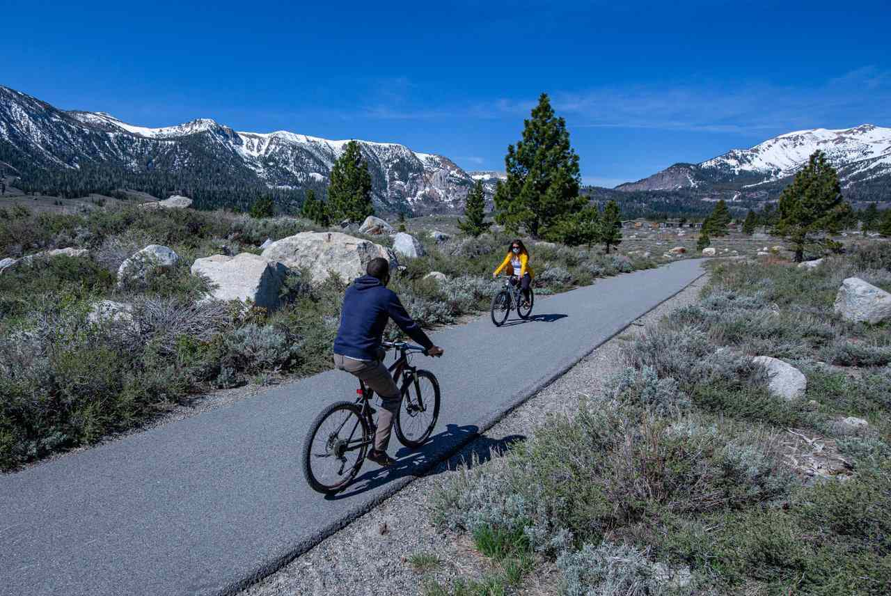 Two people riding bikes on a trail in opposite direction with rocky vegetation and snow covered mountains in the distance