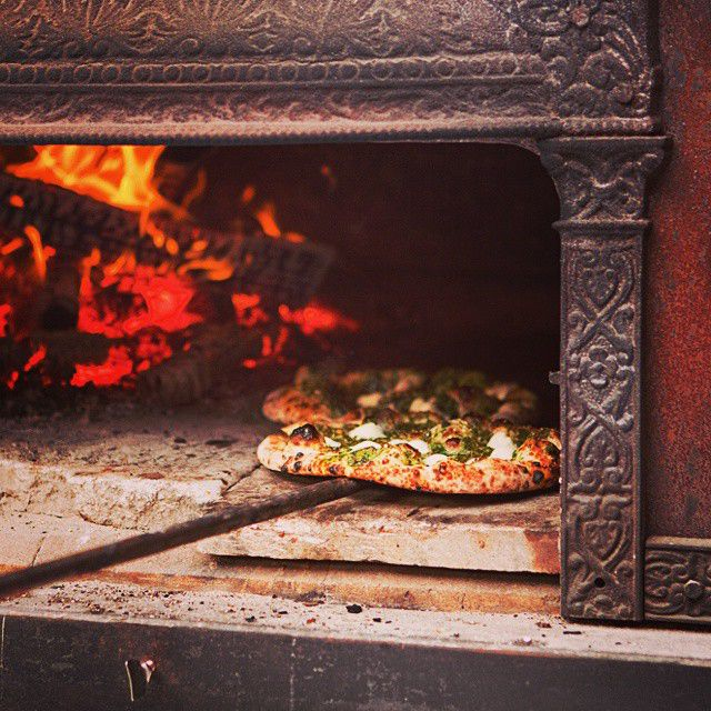Pizza cocinada en horno de leña
