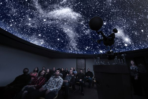 A picture of a planetarium full of people in the middle of show