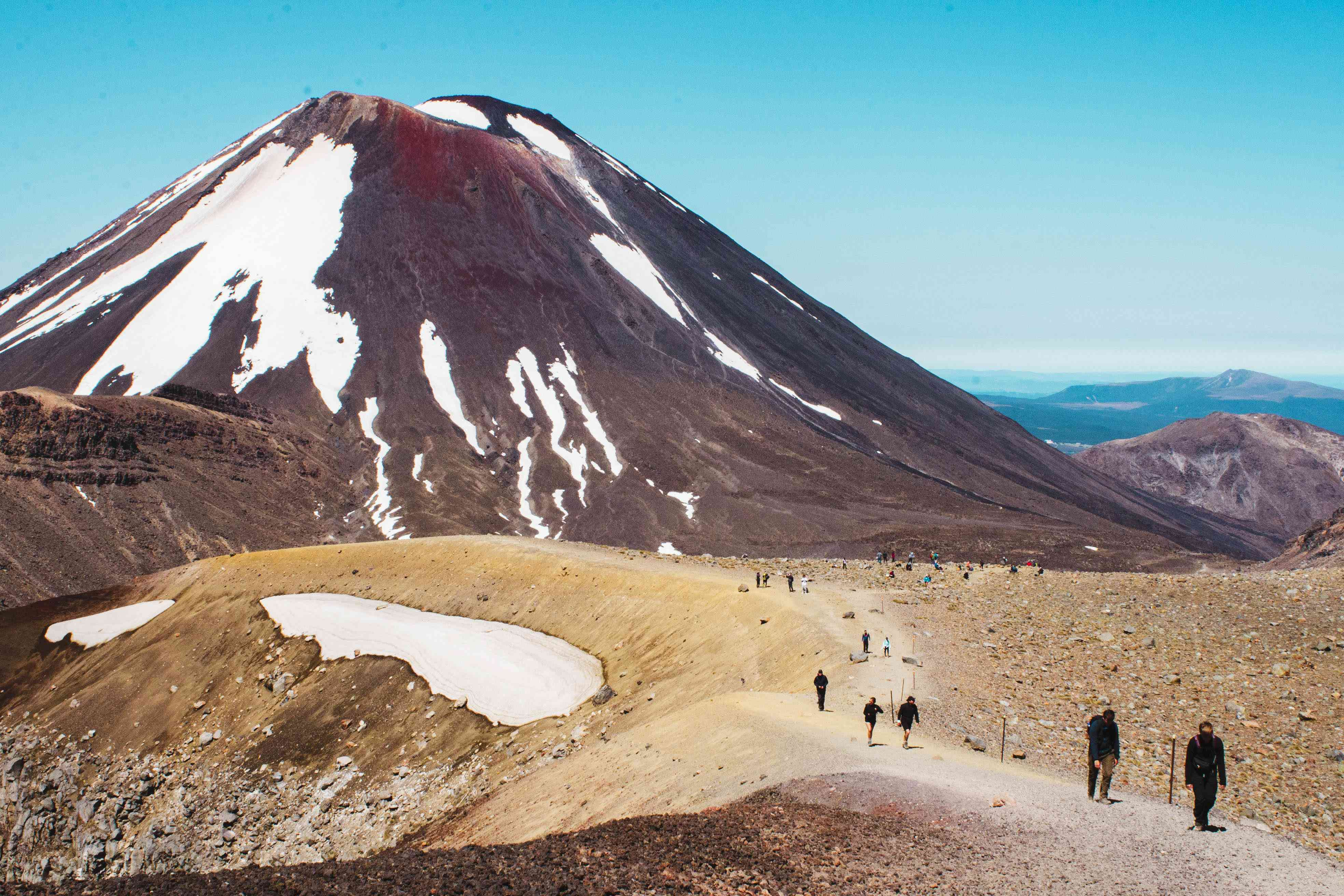 People hiking a path from the mountain in Tongariro