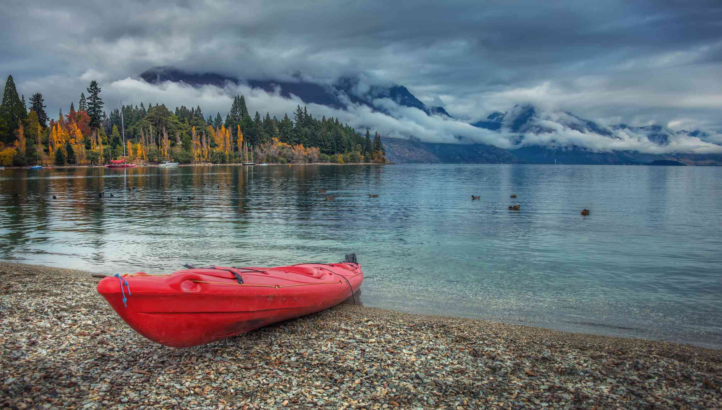 red kayak on stony beach beside calm blue lake with trees, clouds and mountains in background