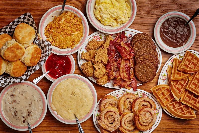 Breakfast spread with chocolate gravy, waffles cut in quarters, cinnamon rolls, scrambled eggs, buscuits, fried chicken, bacon, sausage patties, grits, white gravy, strawberry jam and cornflakes served family style