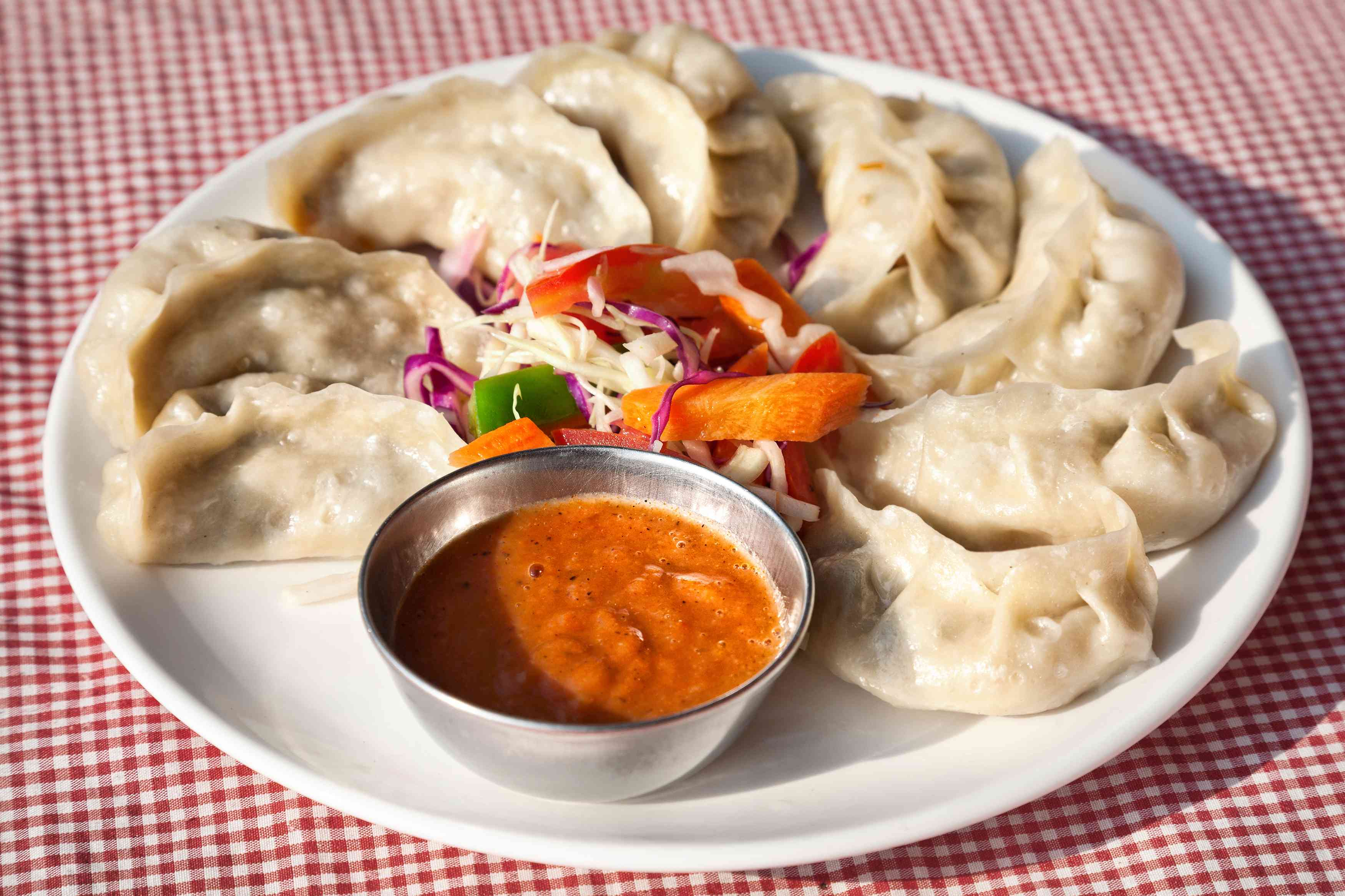plate of crescent-shaped dumplings with a small salad and bowl of orange sauce