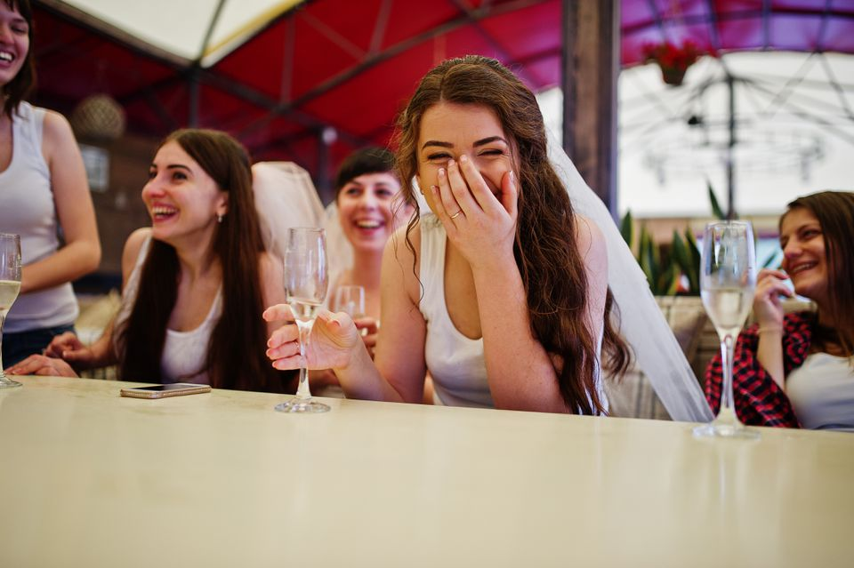 Group of cheerful girls at white shirts sitting at table and drink champagne on hen party.
