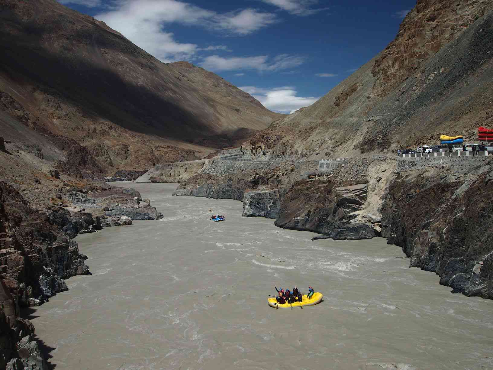 rafts floating on a grey river surrounded by brown mountains