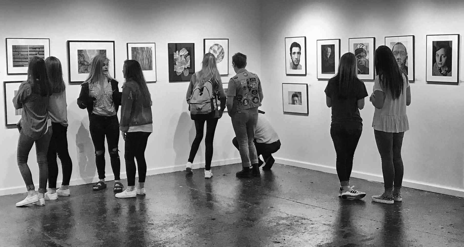 Black and white photos of a group of people looking a photography in a gallery