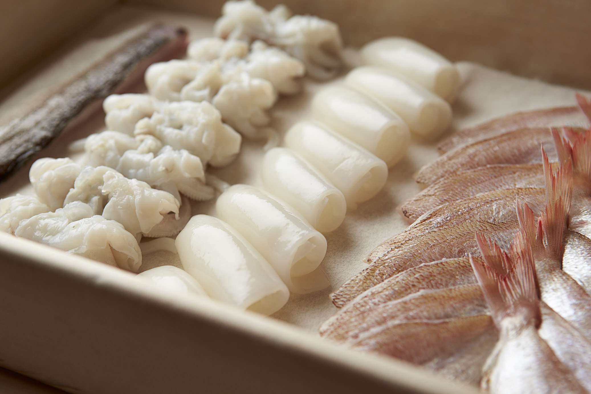 Wooden box with neatly arranged rows of sashimi