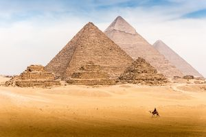 Lone camel and rider in front of the Pyramids of Giza, Egypt