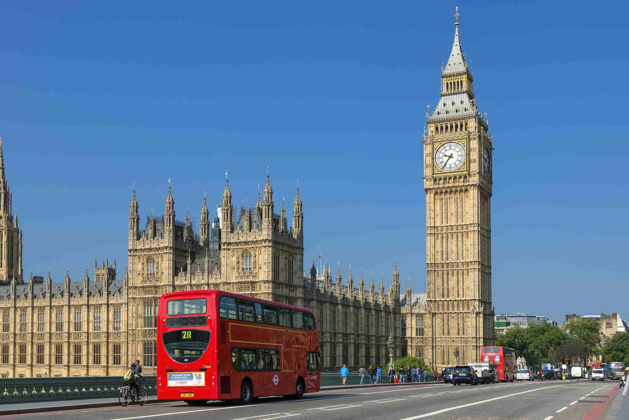 Big Ben Tower in London with double-decker bus traveling in front.