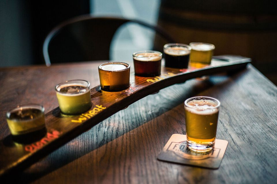 beer sampler with 6 large shot glasses of different beers place on a curved wooden tray. one small of beer is on a coaster infront of the tray