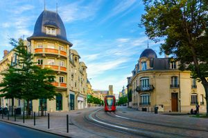 Tram on the streets and Architecture of Reims a city in the Champagne-Ardenne region of France.