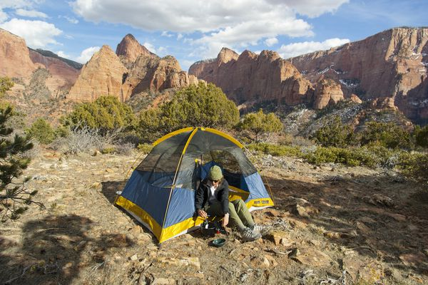 A backpacker cooks a meal beside a small tent with sandstone cliffs in the background.
