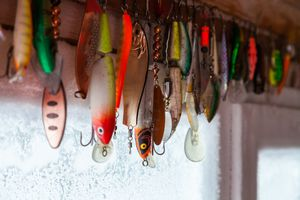 Set of different fishing hooks and lures hanging against a window in the frost