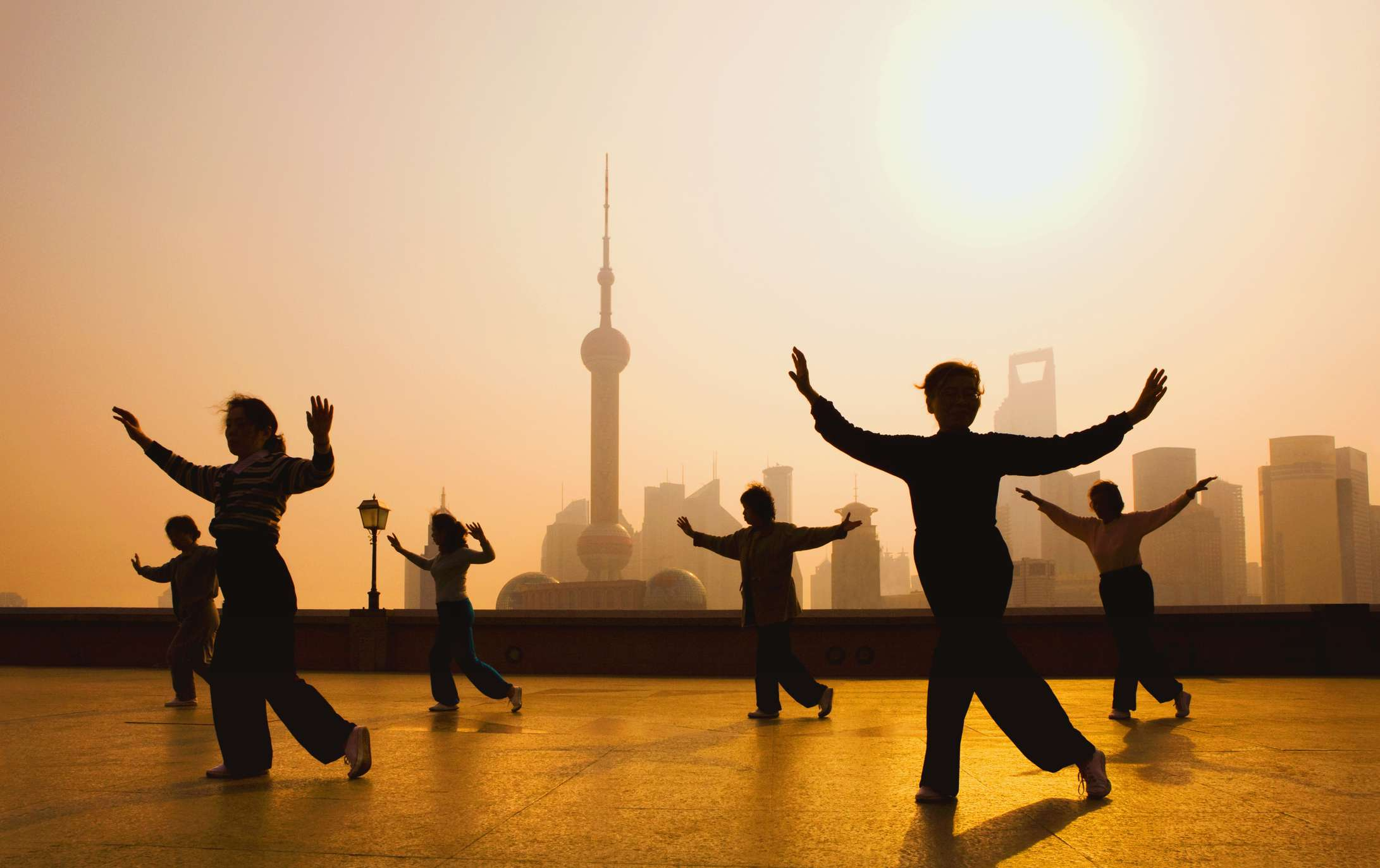 People practicing tai chi on the Bund. Oriental Pearl Tower and Pudong skyline in background.
