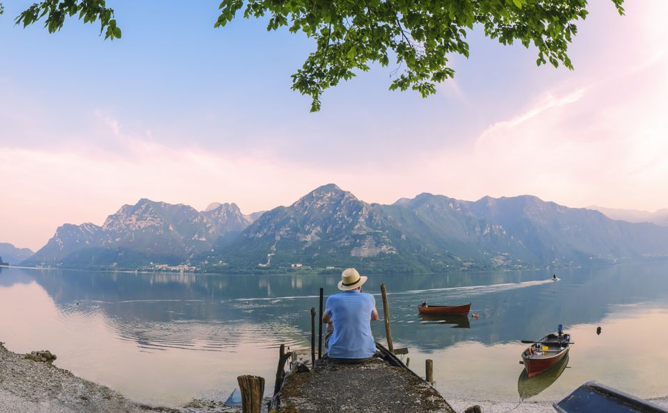 back view of man sitting on jetty at Lake Idro in Lombardy, Italy at morning twilight