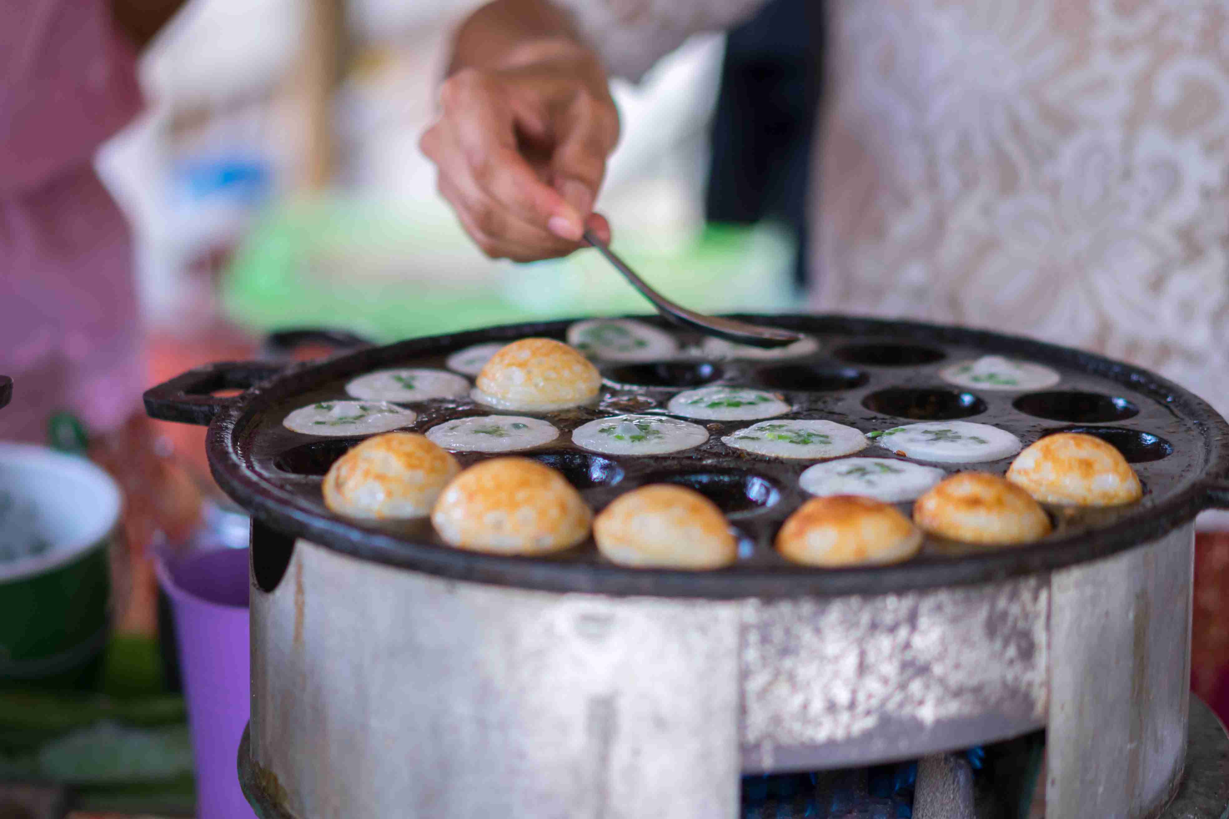 A vendor making kanom krok coconut pancakes in Thailand