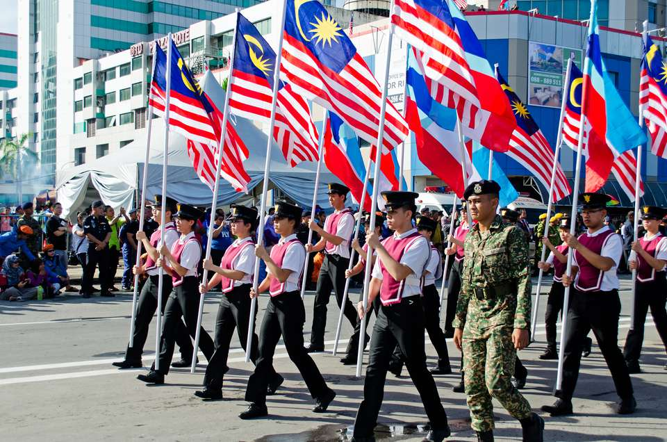People carry Malaysian flags in a Hari Merdeka independence day parade