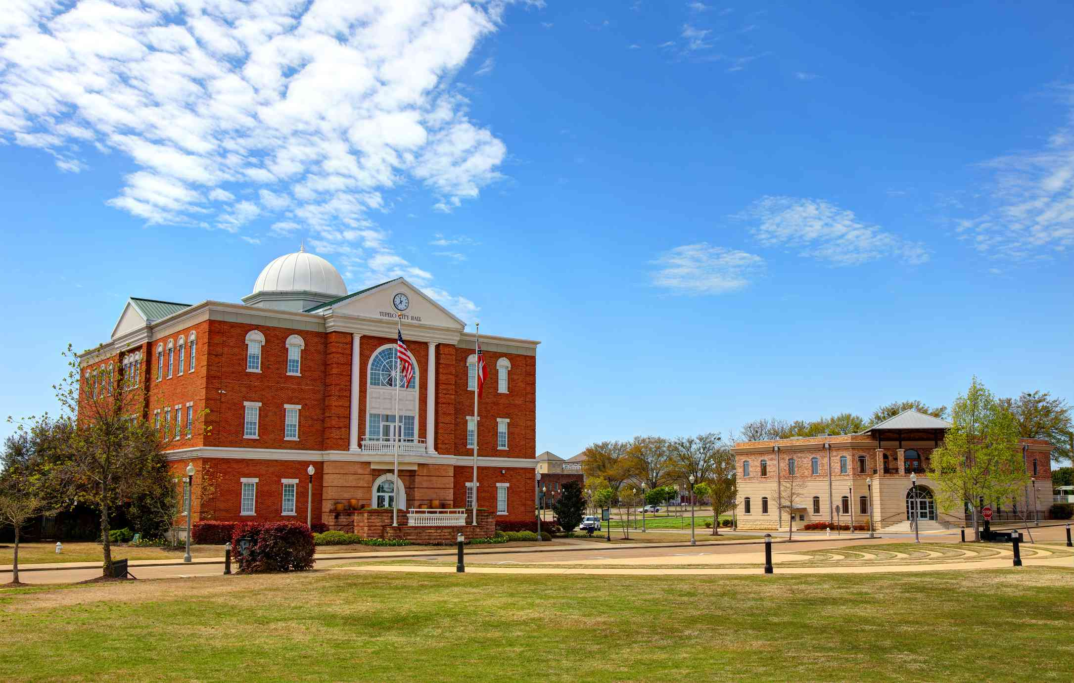 red brick city hall in front of an empty field on a clear day