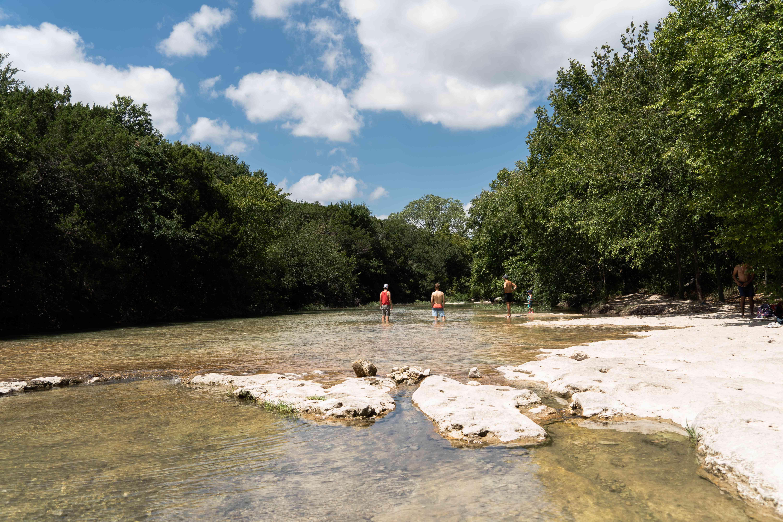 Gente de pie en el agua que corre junto al Greenbelt