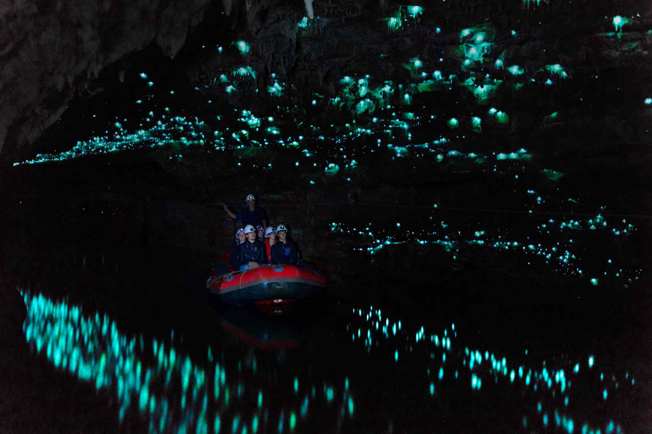 raft with passengers floating through a dark cave with glowworms
