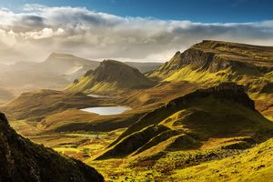 Scenic view of Quiraing mountains in Isle of Skye, Scottish highlands, United Kingdom. Sunrise time with colourful an rayini clouds in background