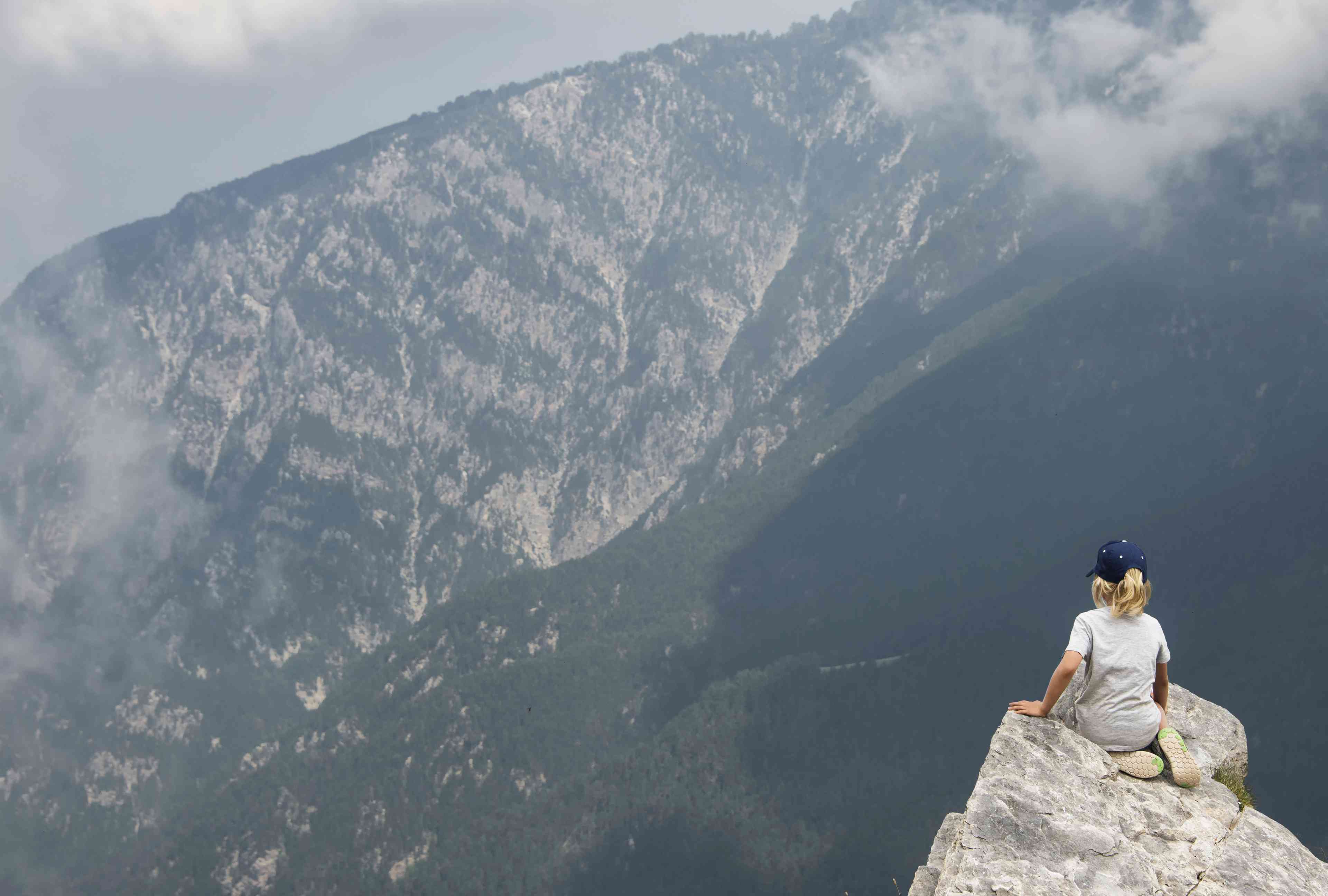 Excursionista de chico mira desde la cresta de la cresta alta, Monte Olimpo, hogar del dioses de la antigua Grecia